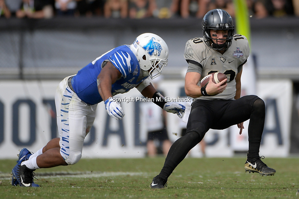 Central Florida quarterback McKenzie Milton (10) scrambles for yardage during the first half of the American Athletic Conference championship NCAA college football game against Memphis Saturday, Dec. 2, 2017, in Orlando, Fla. (Photo by Phelan M. Ebenhack)