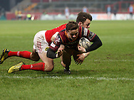 Hallam Amos of the Dragons dives in and scores a try despite the effort of Darren Sweetnam to stop him.<br /> Guinness Pro12 rugby match, Munster v Newport Gwent Dragons at Thomond Park in Limerick , Ireland on Saturday 5th March 2016.<br /> pic by  John Halas, Andrew Orchard sports photography.