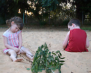 2 children boy aged 5 and girl aged 3 playing in a sand box during a quarrel - Model release available