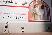 Dubai Foreign resident walking past billboard Ad  on Sheik Zayed highway