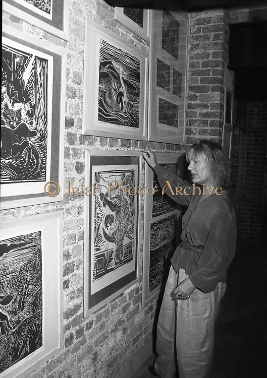 """Pauline Bewick Art Exhibition..1986..03.06.1986..06.03.1986..3rd June 1986..At the Guinness Hop Store,Dublin,artist Pauline Bewick is having an exhibition of her work.The exhibition called """"2 to 50 years""""is a display of her work from age 2 to the present.the art work ranges from simple pencil sketches to more complex paintings and lino cuts...Photograph of the artist,Pauline Bewick,adjusting one of her lino cuts which is displayed on the wall of The hop Store,Dublin"""