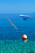 Mooring lines and buouys with jet-ski in distance, beach at Zlatni Rat, near Bol, island of Brac, Croatia
