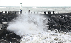© Licensed to London News Pictures. 27/04/2019. West Bay, UK. People walking on the sea front at West Bay in Dorset feel the force of storm Hannah as winds and rain hit the coast. Photo credit: Jason Bryant/LNP