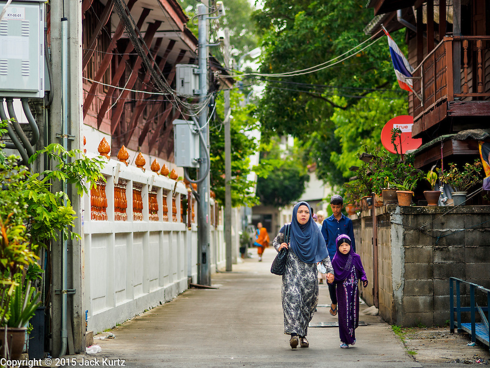 17 JULY 2015 - BANGKOK, THAILAND:     A woman and her daughter walk to Ton Son Mosque in Bangkok for Eid al-Fitr services. Eid al-Fitr is also called Feast of Breaking the Fast, the Sugar Feast, Bayram (Bajram), the Sweet Festival or Hari Raya Puasa and the Lesser Eid. It is an important Muslim religious holiday that marks the end of Ramadan, the Islamic holy month of fasting. Muslims are not allowed to fast on Eid. The holiday celebrates the conclusion of the 29 or 30 days of dawn-to-sunset fasting Muslims do during the month of Ramadan. Islam is the second largest religion in Thailand. Government sources say about 5% of Thais are Muslim, many in the Muslim community say the number is closer to 10%.          PHOTO BY JACK KURTZ
