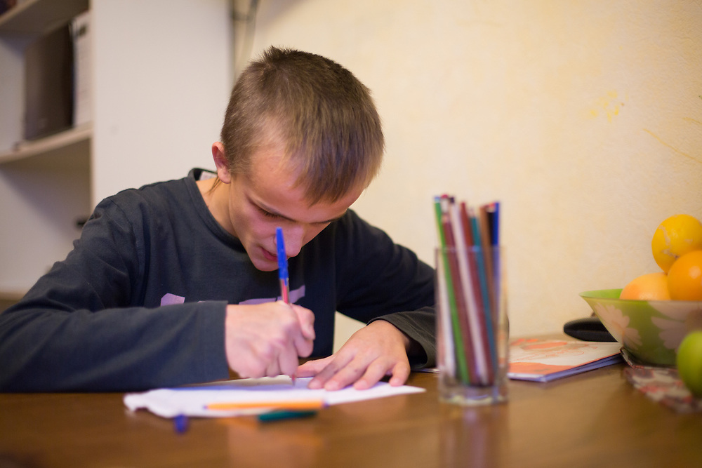 """CAPTION: Dima, who struggles with hyperactivity, focuses his attention for a while on frenetic scribbling. Though her love for him is palpable, his mother is pushed to her limits with caring for him. While her husband has left him, her closest family members have passed away. This is why the Short Break Service provided by Partnership For Every Child (P4EC) means so much to her. """"This service has saved my family"""" she says through teary eyes. NAMES MUST BE CHANGED. LOCATION: St Petersburg, Russia. INDIVIDUAL(S) PHOTOGRAPHED: Nikolay Grigoryev."""
