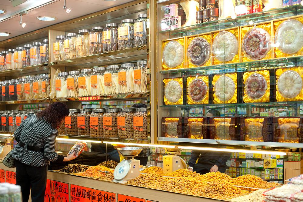 Central district, Hong Kong island, Hong Kong, China, Asia - A woman shopping at traditional store of dry food.