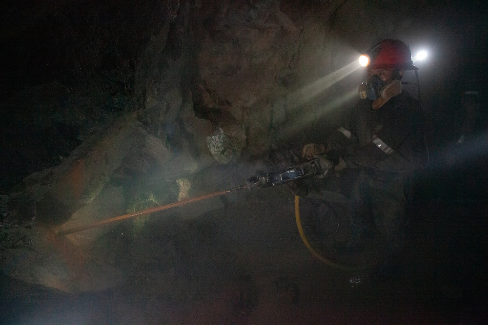 A lead miner drills into rock underground at the SOTRAMI mine in Ayacucho.