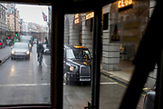 A London taxi cab is seen through the rear window of a Routemaster bus as it drives past the Ritz on Piccadilly, on 17th October 2019, in London, England.