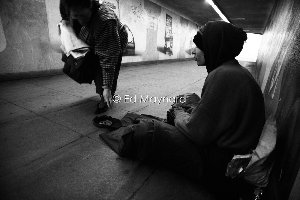 A women drops some lose change into the hat of a young man begging in a subway, Birmingham, West Midlands, England, UK.