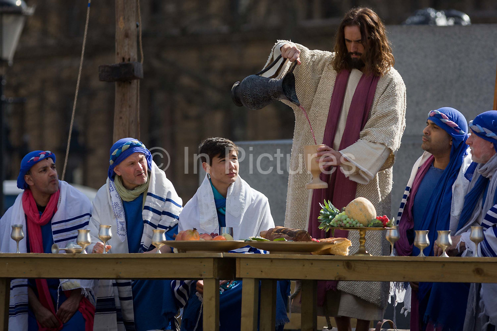 London, 25th March 2016: The scene of The Last Supper during The Passion of Jesus which is performed in Londons Trafalgar Square by members of Wintershall Trust. Played annually on Good Friday it celebrates the cruxifixion and resurrection of Jesus Christ. The cast re-enacts the Christian Biblical story to an audience of thousands and the main character is played by professional actor James Burke-Dunsmore.