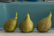 Three figs on the edge of the sink.