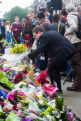 Parliament Square, Westminster, London, June 17th 2016. Following the murder of Jo Cox MP friends and members of the public lay flowers, light candles and leave notes of condolence and love in Parliament Square, opposite the House of Commons. PICTURED: A man lays a bouquet of flowers among the many others.