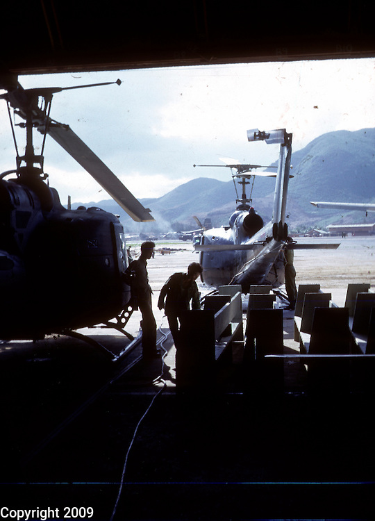 Workers repair helicopters in a hangar at An Khe in November 1966. This images is from the collection of J.W. Womble of the 610th Transportation Company during the Vietnam War.