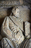 """Early Anglo Saxon sulptures of an Apostle holding a book now part of the south porch of Malmesbury Abbey, Wiltshire, England. The apostles, apart from Peter who holds a crude key, have no distinguishing feature to allow identification. Some are holding books, none have halos and some hold their heads at awkward angles. These three styles are typical of Anglo Saxon art. The two panels are 10 ft long and 4ft 6"""" high are date from the original Ango Saxon church of 705. They were probablbly built into the proch during the Norman rebuilding. The style of these sculptures is of the Roman Byzantine style and were probably sculpted by masions from Gaul.  Malmesbury Abbey, Wiltshire, England"""