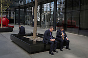 Businessmen check messages outside a financial institution in the Square Mile, on 3rd March 2017, in the City of London, England.
