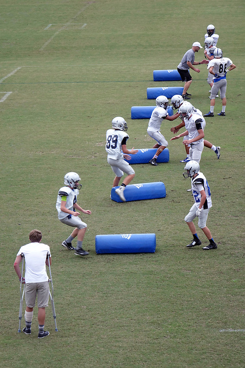 USA, United States, Florida, Jacksonville; American Football practice at Bartram Trail. An injured player on crutches watches a football training  