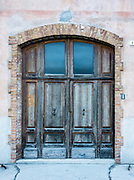 Old wooden double doors are framed by brick, in Calalzo di Cadore village, Dolomites mountains, in Belluno province, Veneto region, Italy, Europe. The painter Titian was born in the adjacent town of Pieve di Cadore around 1488-1490.