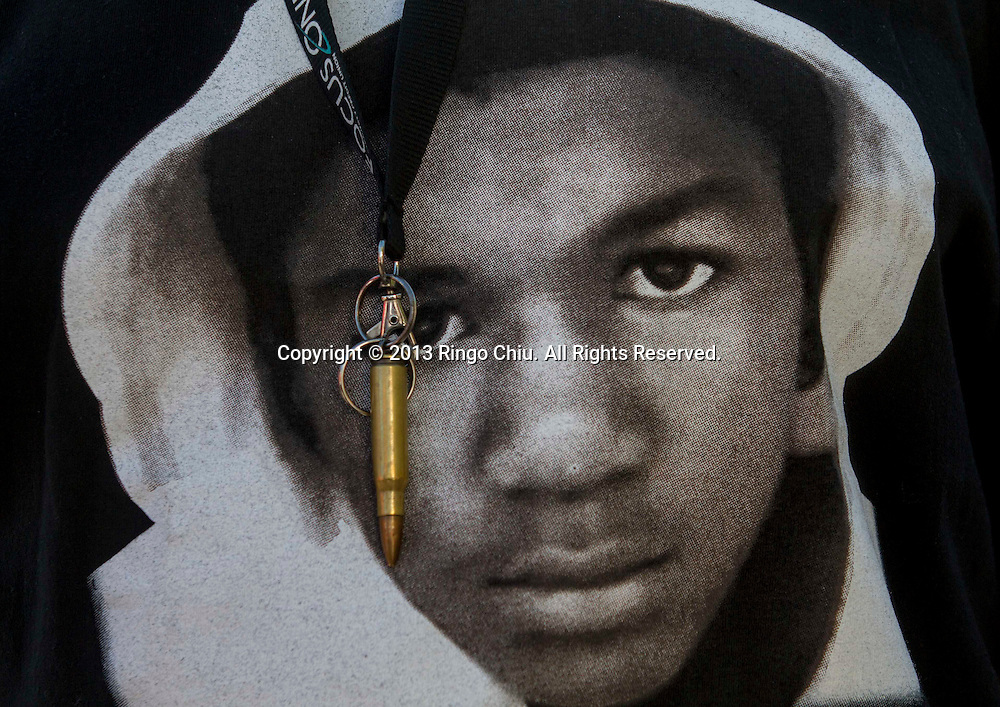 """7月15日,一弹壳钥匙扣挂在身穿印有特雷翁·马丁图像体恤衫的示威者胸前。在美国加利福尼亚州洛杉矶,大批民众走上街头,抗议陪审团关于乔治·齐默尔曼无罪的判决。白人协警齐默尔曼于2012年2月在佛罗里达州小城 桑福德因""""形迹可疑""""射杀了手无寸铁的黑人少年特雷翁·马丁。佛罗里达州一个陪审团於7月13日深夜判定,枪杀黑人少年特雷翁·马丁的被告人乔治·齐默尔曼无罪本。(新华社发 赵汉荣摄)<br /> An image of Trayvon Martin and a bullet shell keychain hanging from a protester's lanyard are seen during a demonstration to protest George Zimmerman's acquittal in the shooting death of Florida teen Trayvon Martin, on Monday July 15, 2013 in Los Angeles, California. Seventeen-year-old Martin was shot and killed in February 2012 by neighborhood watch volunteer George Zimmerman.(Photo by Ringo Chiu/PHOTOFORMULA.com)"""