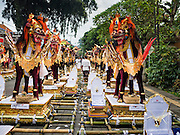 16 JULY 2016 - UBUD, BALI, INDONESIA: A man walks among the sarcophagi that were used in the mass cremation in Ubud Saturday. Local people in Ubud exhumed the remains of family members and burned their remains in a mass cremation ceremony Wednesday. Almost 100 people were cremated and laid to rest in the largest mass cremation in Bali in years this week. Most of the people on Bali are Hindus. Traditional cremations in Bali are very expensive, so communities usually hold one mass cremation approximately every five years. The cremation in Ubud concluded Saturday, with a large community ceremony.     PHOTO BY JACK KURTZ