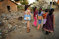 Sisters Shrianna and Brianna Barthelot, 11 and 13, walk past a pile of garbage to church with relatives, Batticaloa, Sri Lanka, July 10, 2005. The sisters lost both parents and their older brother in the tsunami. They are now living with relatives at night and spending most of their days at the convent where the rest of their village is staying. Residents of the small Christian village Dutch Bar spent more than six weeks in a makeshift refugee camp at the local convent recovering from the devastating tsunami that hit the eastern and southern borders of Sri Lanka. They were then moved into another temporary living camp, while awaiting the building of new homes. More than 150 members in this community of less than 1000 people died in the tragic event.