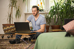 Mid adult man working on laptop in living room, Munich, Bavaria, Germany