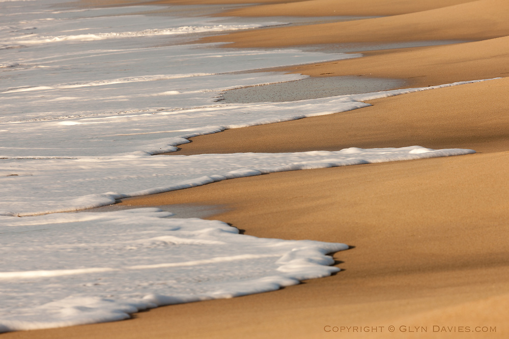 Almost cream-like, wonderful tongues of foamy ocean lick the ice-cream wafer sand