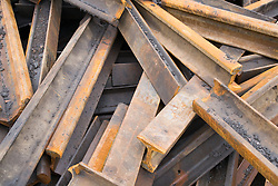 Pile of discarded old steel rails at a metal recycling centre,