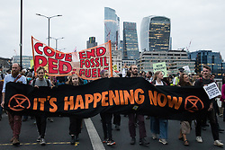 London, UK. 2nd September, 2021. Environmental activists cross London Bridge after marching out of the City of London following a blockade of the Bank of England on the eleventh day of their Impossible Rebellion protests. The activists included over fifty wearing signs indicating that they were breaking restrictive bail conditions by entering the City of London. Extinction Rebellion are calling on the UK government to cease all new fossil fuel investment with immediate effect.