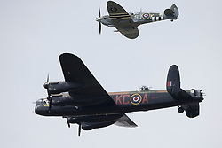 © Licensed to London News Pictures. 12/07/2014. RAF Fairford UK. The BBMF Lancaster and Spitfire Performs at the Royal International Air Tattoo at RAF Fairford. Photo credit : Ian Schofield/LNP