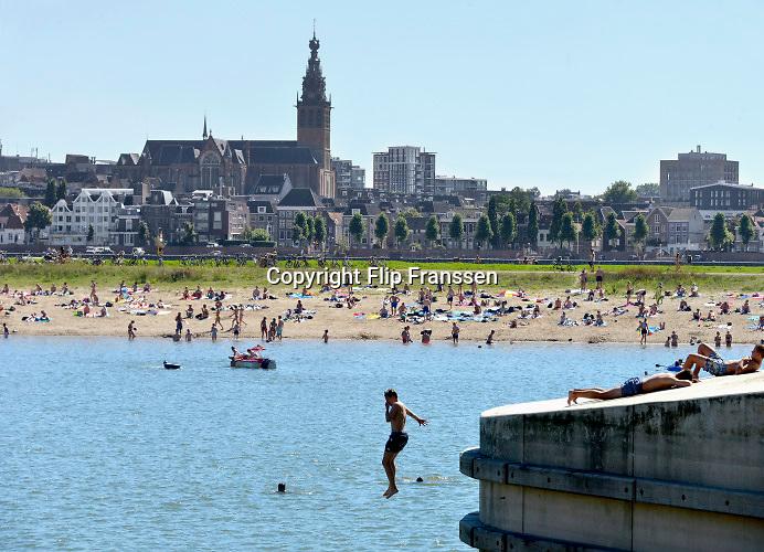Nederland, nijmegen, 26-8-2018Mensen trekken massaal naar de oevers van de waal en de spiegelwaal in het rivierpark aan de overkant van Nijmegen . Het nieuwe recreatiegebied is een aanwinst voor de stad en omgeving.  Springen vanaf een hoge brugpijler in  het water .Foto: Flip Franssen