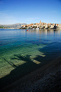 Korcula old town viewed from the West, with shadows on water and beach in foreground. Korcula old town, island of Korcula, Croatia