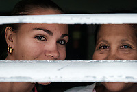 SANTIAGO DE CUBA, CUBA - CIRCA JANUARY 2020: Portrait of Cuban women peaking thru a window in Cayo Granma, and island close to  Santiago de Cuba