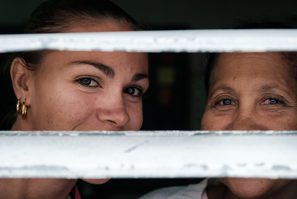 SANTIAGO DE CUBA, CUBA - CIRCA JANUARY 2020: Portrait of Cuban women peaking thru a window in Cayo Granma, and island close to  Santiago de Cuba