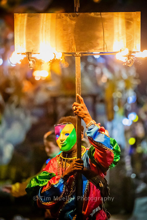 A masked flambeaux walker lights the way for the Krewe of Hermes as they parade through uptown New Orleans.
