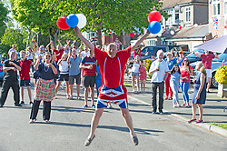 ©Licensed to London News Pictures 08/05/2020  <br /> Orpington, UK. 62 year old black cabbie Tony Boon holding balloons and jumping for joy with his Broughton road neighbours from Orpington in the background.  VE-Day 75th anniversary celebrations in coronavirus lockdown. People enjoy parties in their front gardens with family and neighbours as they observe social distancing. Photo credit:Grant Falvey/LNP