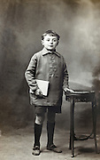 classical vintage studio portrait photo of a full length standing school boy