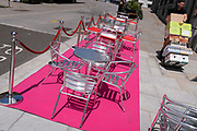 A man pushes a trolley with retail supplies, past a pink carpet with silver street tables and seating which stretches uphill in Aldwych, on 23rd June 2021, in Westminster, London, England.