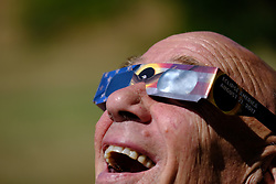 Mike Daglen watches as the moon obscures the sun during the total solar eclipse in Dallas Ore., on August 21, 2017. (Photo by Alex Milan Tracy)