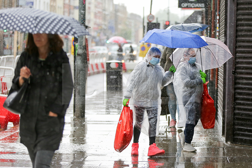© Licensed to London News Pictures. 18/06/2020. London, UK. Members of the public shelter from heavy rain underneath umbrellas in north London.  Photo credit: Dinendra Haria/LNP