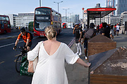 In the week that many more Londoners returned to their office workplaces after the Covid pandemic and the summer holidays, a woman waits for a bus as commuters and public transport make their way southwards at the southern end of London Bridge in Southwark, on 8th September 2021, in London, England.