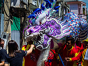 """02 JUNE 2017 - SAMUT SAKHON, THAILAND: Dragon dancers perform during the parade for the City Pillar Shrine in Samut Sakhon. The Chaopho Lak Mueang Procession (City Pillar Shrine Procession) is a religious festival that takes place in June in front of city hall in Samut Sakhon. The """"Chaopho Lak Mueang"""" is  placed on a fishing boat and taken across the Tha Chin River from Talat Maha Chai to Tha Chalom in the area of Wat Suwannaram and then paraded through the community before returning to the temple in Samut Sakhon. Samut Sakhon is always known by its historic name of Mahachai.      PHOTO BY JACK KURTZ"""