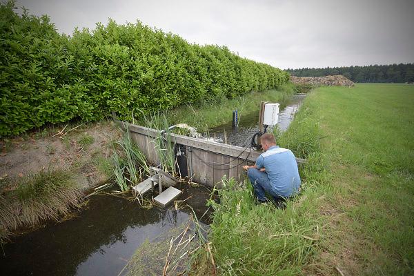 Nederland, Ommen, 4-6-2018Een boer controleert een zogenaamde sawax, een slim stuwtje wat zelf de waterstand regelt op een vooringesteld niveau. Indien nodig kan ook met een pomp het waterniveau in de sloot geregeld worden .
