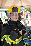 Boy age 11 wearing firefighter jacket and helmet at rescue demonstration. Aquatennial Beach Bash Minneapolis Minnesota USA