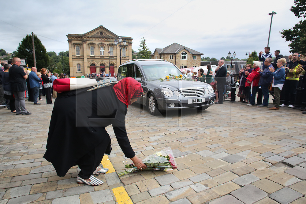 © Licensed to London News Pictures. 15/07/2016. Batley, UK. A woman lays down flowers as Jo Cox's funeral cortege passes through her hometown of Batley, West Yorkshire. The Labour MP was stabbed and shot in the street as she left her constituency surgery last month. Thomas Mair was arrested in connection with the murder and is set to face trial this year.  Photo credit : Ian Hinchliffe/LNP
