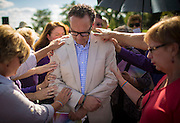 Parishioners bless Colin Collette during a vigil to support him Sunday, Sept. 7, 2014 outside Holy Family Catholic Parish in Inverness. Collette was the music director of the church until he was fired recently after becoming engaged to his same-sex partner.   (Brian Cassella/Chicago Tribune)