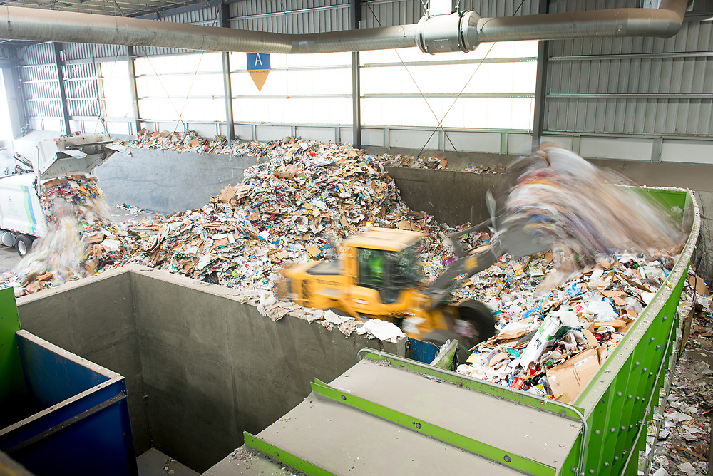 A truck unloads consumer recyclables and a front end loader transfers those recyclables to the sorting inflow area.
