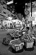 Women selling fruit at night, from edge of the street opposite Binh Thanh Market. Ho Chi Minh City (Saigon), Vietnam