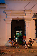 """Colonial-era buildings along the """"calle del medio"""".People sitting on the rocking chairs"""