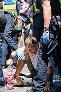 Police assist a protester who had been sprayed with capsicum spray in front of the state parliament. The groups who have organised the many Freedom Day protest over the last 3 months, attempted to march to State Parliament on Melbourne Cup Day demanding the sacking of Premier Daniel Andrews for the lockdown and attacks on their civil liberties, where they were met with a heavy police presence.  (Photo by Michael Currie/Speed Media)