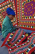 Lao woman stitches bright traditional Lao fabric on Vientiane sidewalk